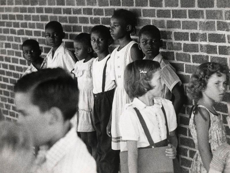 foto preto e branca, no fundo, fila de meninos e meninas negros encostados em uma parede e em primeiro plano, menina e menino brincando.