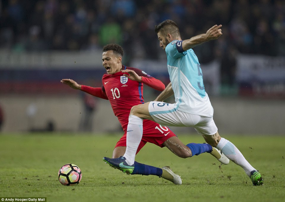 Dele Alli shouts as he goes down under the challenge of Slovenia captain and centre backBostjan Cesar (right)