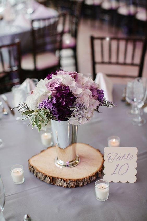 ein schickes blumengesteck mit Rouge, weißen und lila Blüten in einer vase Silber