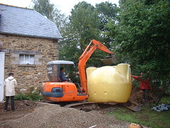 Using the digger to move the septic tank