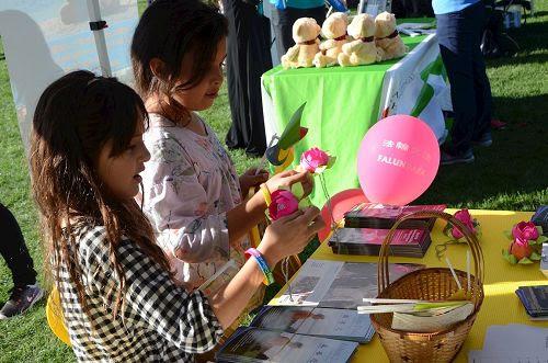 '图4:年轻的女孩子们被法轮功学员展位上摆放的精致莲花吸引'