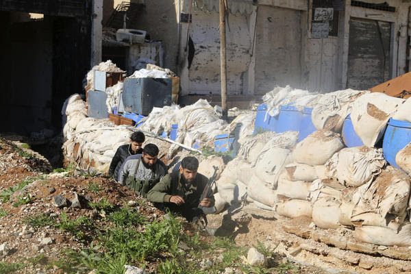 Free Syrian Army fighters run behind sandbags in Daraa Al-Mahata, in southern Syria, on Jan. 21. Many moderate rebels joined the uprising to fight against President Bashar Assad, but the U.S. plans to train them to fight the self-proclaimed Islamic State.