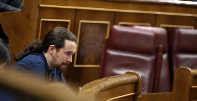 El secretario general de Podemos, Pablo Iglesias, a su escaño durante el pleno del Congreso. EFE/Javier Lizón