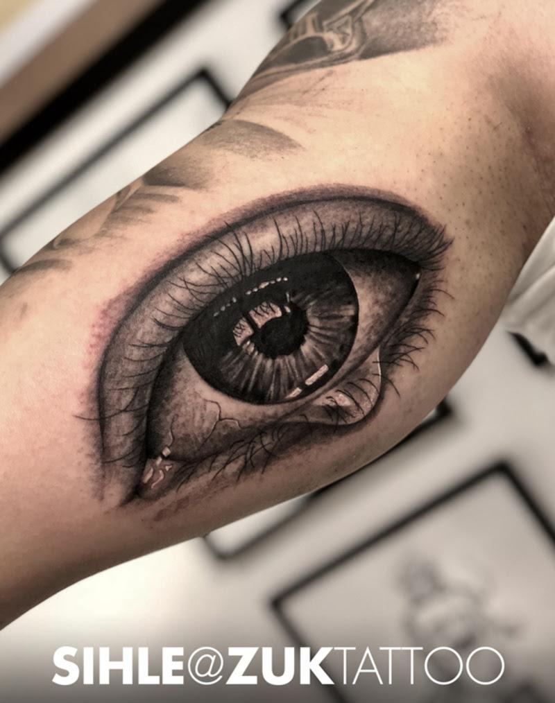 Tatuaje De Un Ojo Realista En Negro Y Gris En El Bíceps
