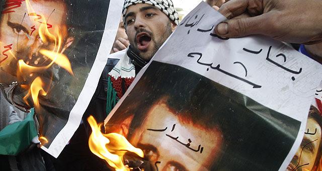 Dos manifestantes queman retratos del presidente sirio, Bashar al Assad. | Reuters