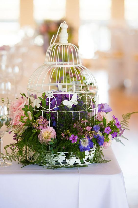 einen weißen Vogelkäfig, der mit grünem laub, die lila und rosa Blüten für einen bunten großen Tag