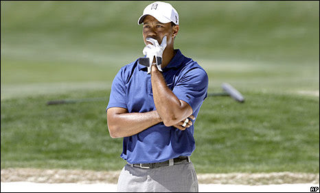 Tiger Woods watches his shot from the bunker