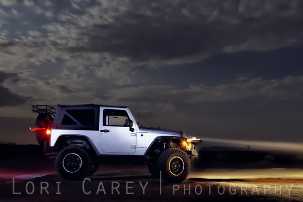Jeep on desert playa at night under full moon, lightpainting
