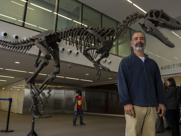 Paleontologista Sebastian Apesteguia posa em Buenos Aires perto da réplica de Gualicho (Foto: EITAN ABRAMOVICH / AFP)