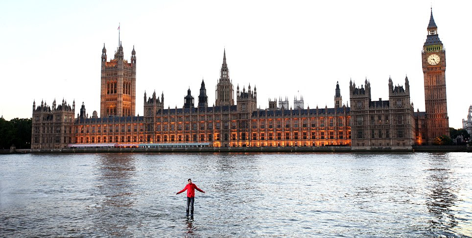 Biblical epic: Magician Dynamo poses while standing in the middle  of the River Thames where he performed an illusion in which he appeared  to walk on water