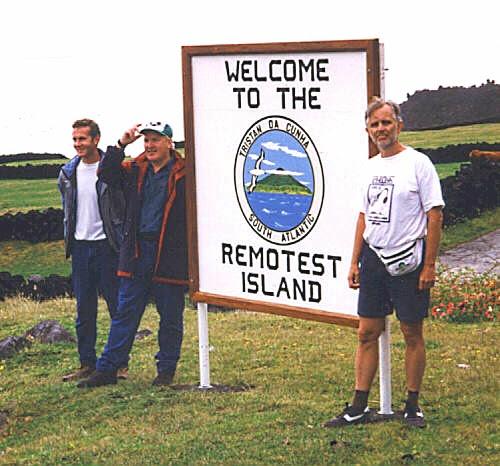 Turistas posando ao lado da placa de boas vindas a Tristão da Cunha