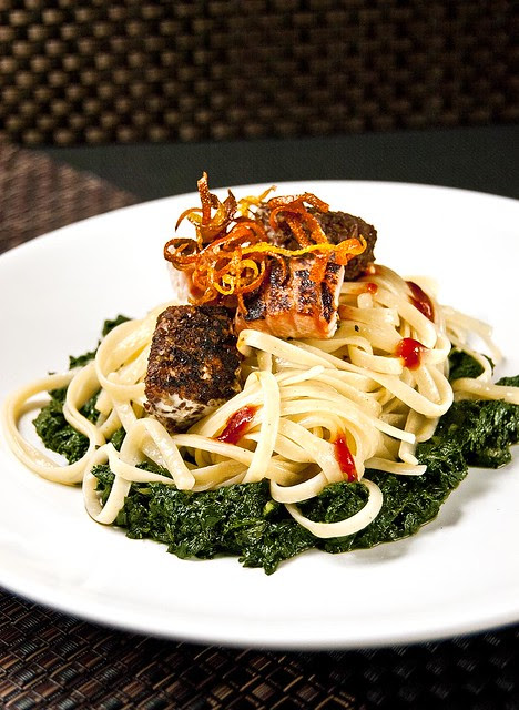 Citrusy-hot linguine on a bed of garlicky spinach served with seared salmon bits and garnished with crispy citrus zests