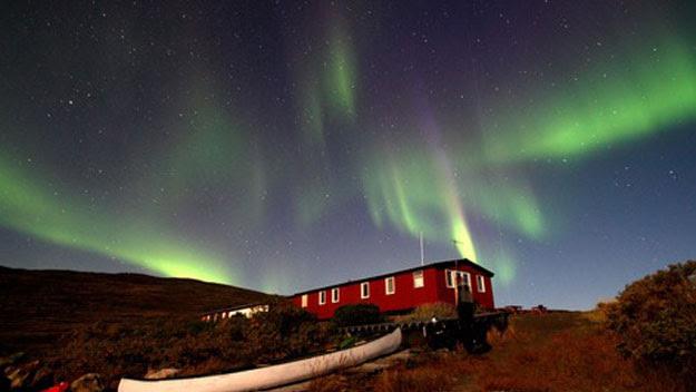 Aurora borealis glows over a hut