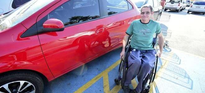 Em um estacionamento, um cadeirante de idade sorri ao lado de um veículo vermelho