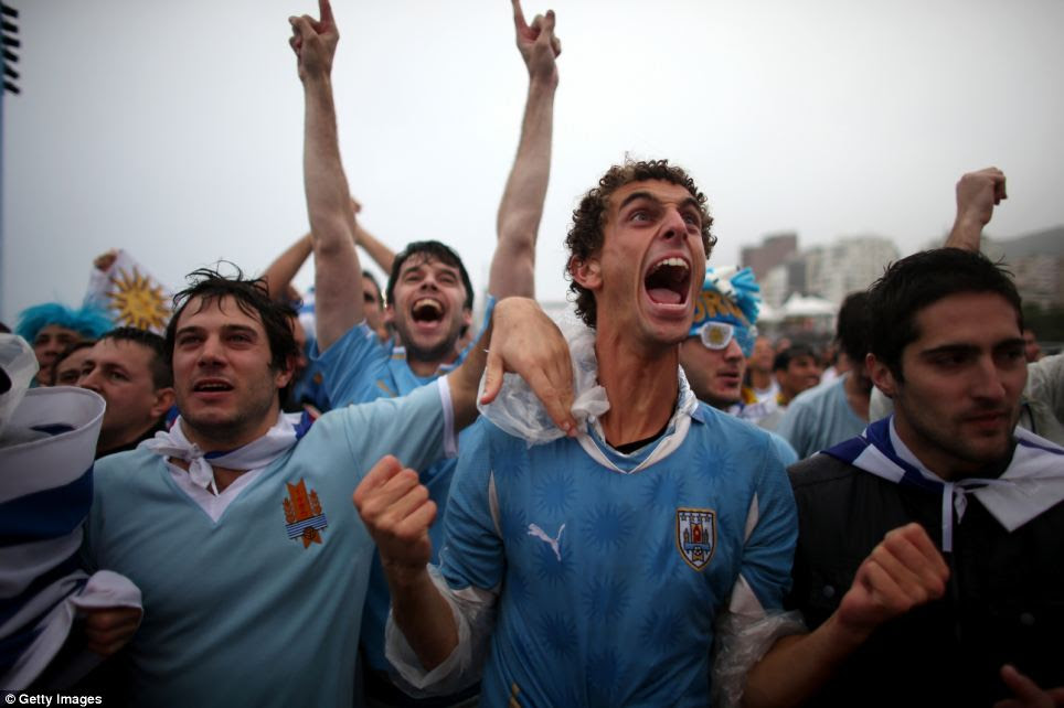 Uruguay fans celebrate as Luis Suarez scores their first goal against England as seen on the screen set up at Word Cup FIFA Fan Fest on Copacabana beach