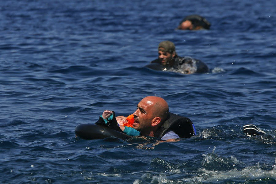 A Syrian refugee holding a baby in a life tube swims towards the shore after their dinghy deflated some 100m away before reaching the Greek island of Lesbos (Alkis Konstantinidis, Thomson Reuters - September 13, 2015).