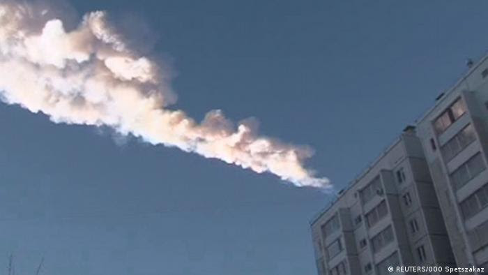 The trail of a falling object is seen above a residential apartment block in the Urals city of Chelyabinsk (Reuters)
