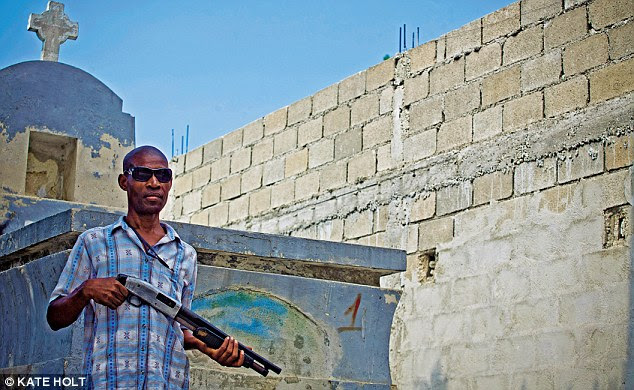 A man with a shotgun guards graves in the main cemetery in Port au Prince. Violent crime and poverty are on the rise in Haiti and graves are regularly raided by people who steal coffins to resell