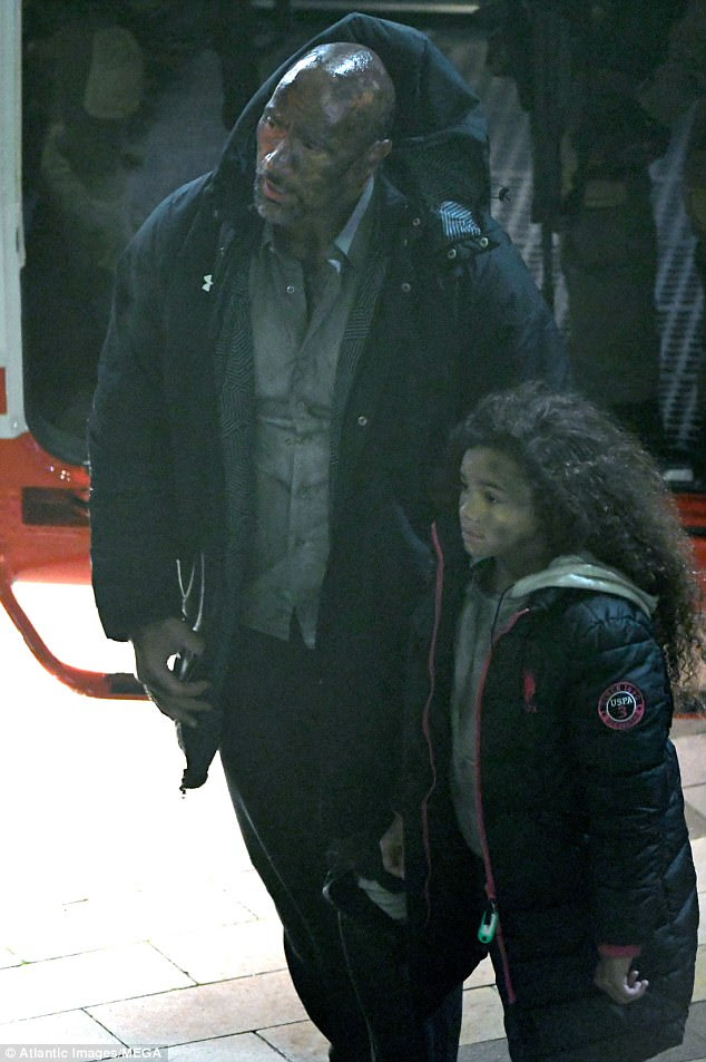 Keeping warm: A little girl named Georgia - played by McKenna Roberts - was seen standing beside Dwayne, both of them bundled up in thick anoraks