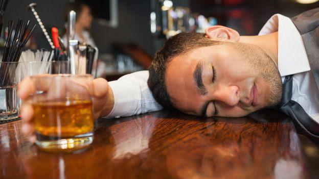 Hombre dormido en mostrador mientras agarra vaso de cerveza