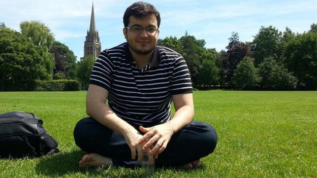 Biólogo Eli Vieira em gramado no Reino Unido