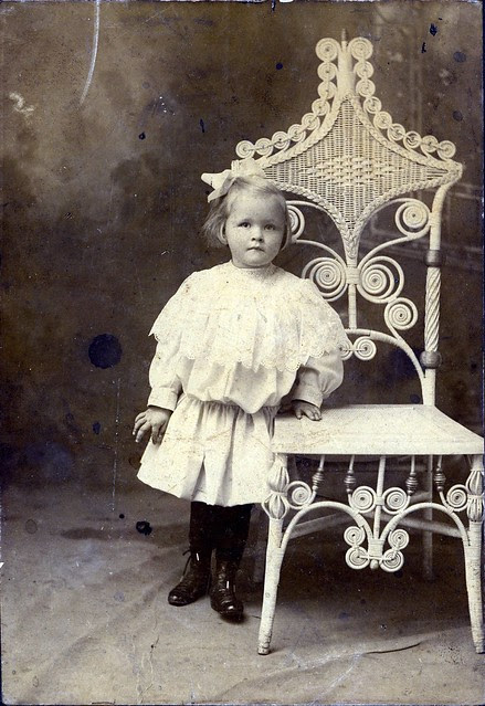 Child with wicker chair