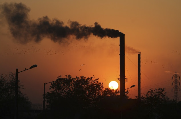 Birds fly past at sun set as smoke emits from a chimney at a factory in Ahmadabad, India, Monday, Dec. 8, 2014. The momentum from a historic U.S.-China pact ...