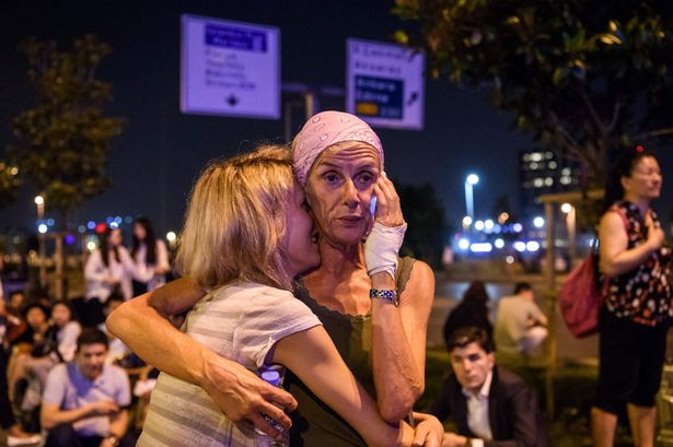 Passengers embrace outside Ataturk airport`s main enterance in Istanbul