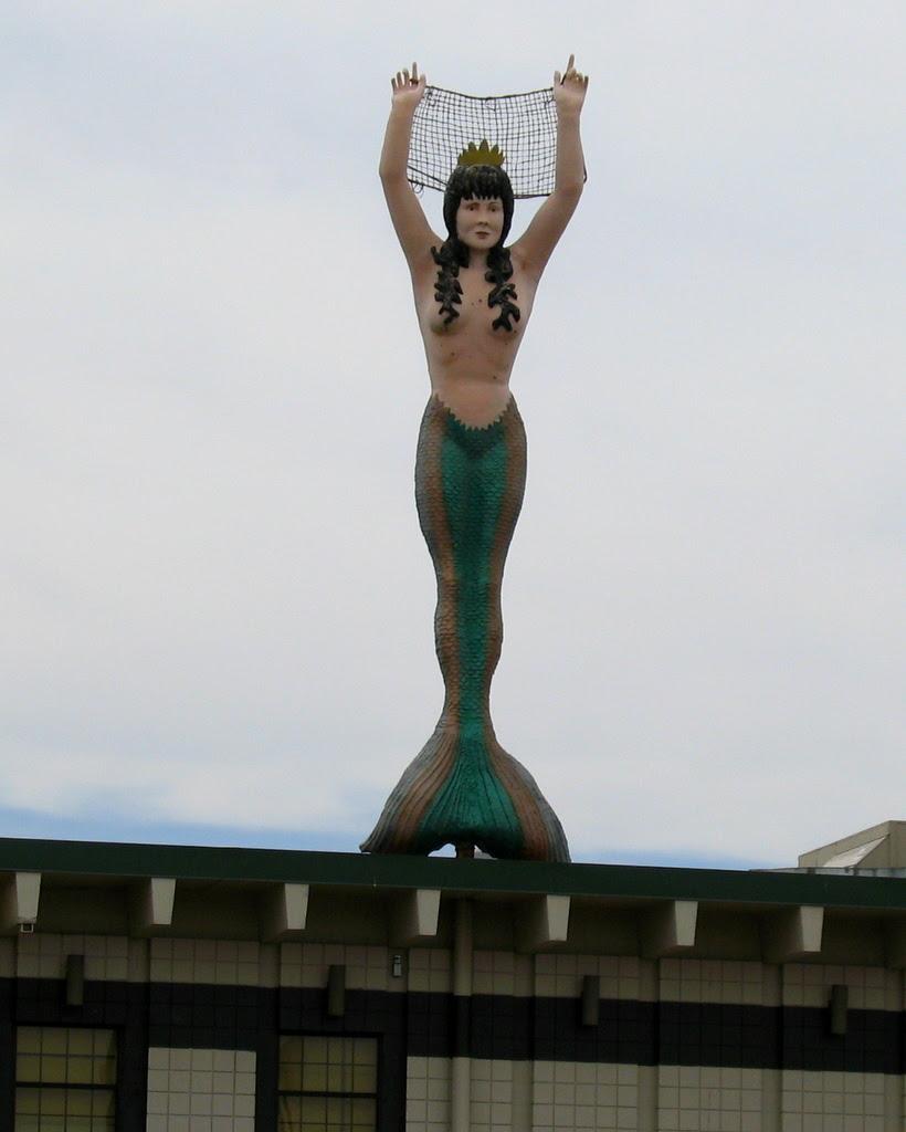 A 30 foot mermaid sits atop the mermaid restaurant.