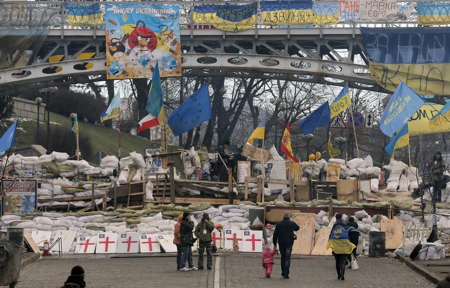 Curiosos observam barricada montada por opositores ao presidente da Ucrânia,  Viktor Yanukovich, na Praça da Independência em Kiev. Milhares de manifestantes tem se reunido no local para protestar contra o governo, por se afastar cada vez mais da UE