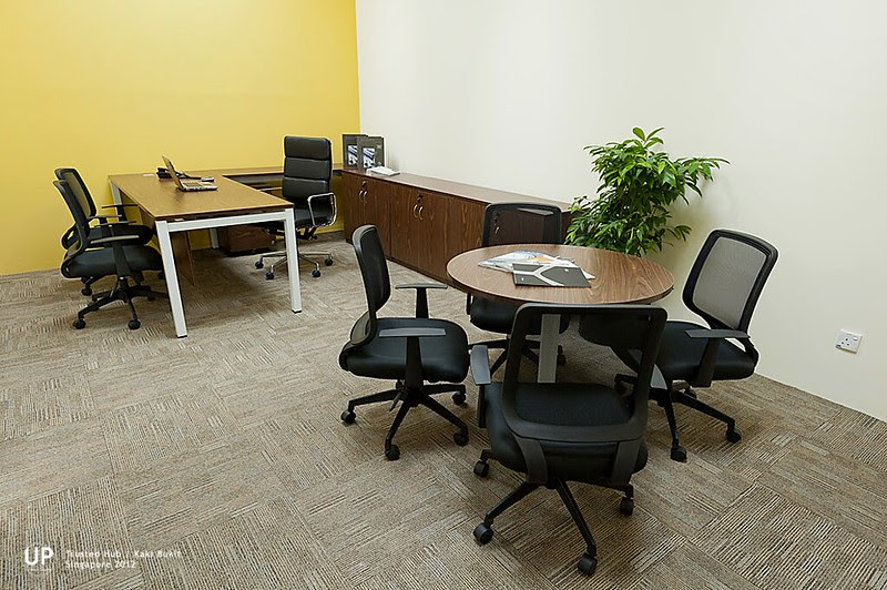 Director room with yellow highlight wall, L shape workstation with drawer pedestral and small round discussion table