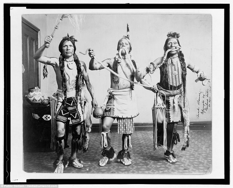 Three Native American men, in traditional clothing, posing as if performing a snake dance in a 1905 photograph