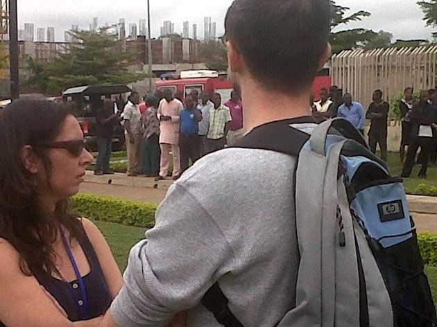 This image released by Saharareporters shows workers standing outside the United Nations' main office in Nigeria's capital Abuja Friday Aug. 26, 2011, after a large explosion flattened one wing of the