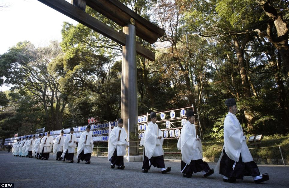 Shinto priests walk under a 'torii' (Japanese gate located at the entrance of a Shinto shrine) after they participated to a shinto ritual in preparation for the New Year at Meiji Shrine in Tokyo, Japan