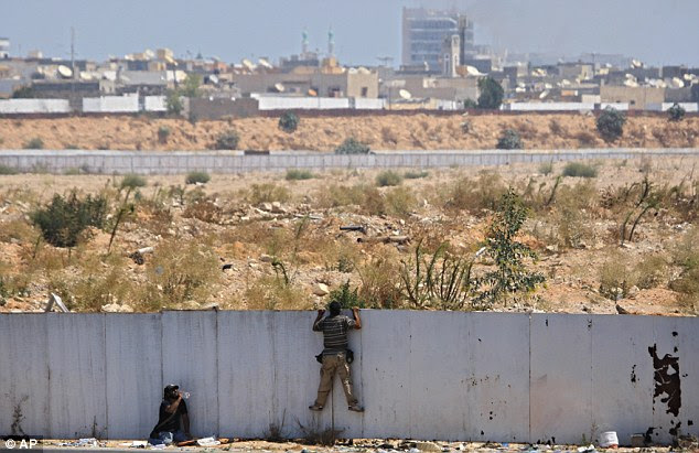 Rebel fighters climb onto a fence to watch the fighting near the main Gaddafi compound as it is pounded with mortars