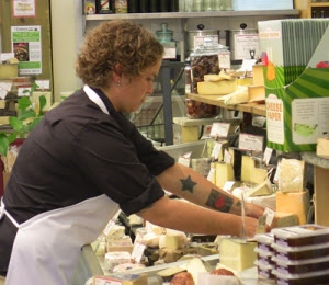Jana Werner arranges cheese case at the Pasta Shop in Berkeley