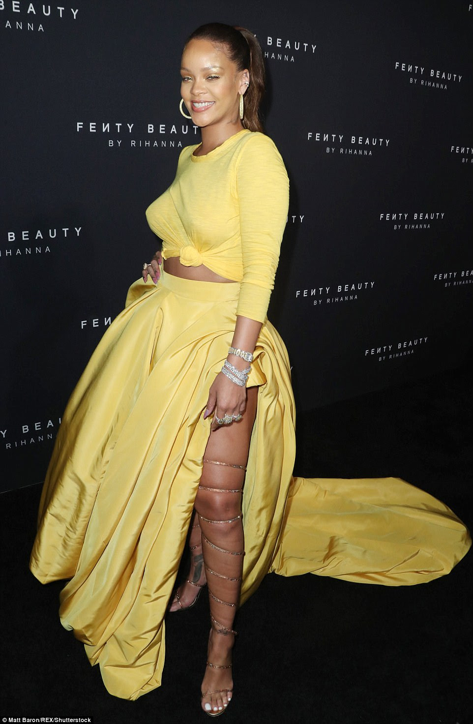 Fashionable choice: She paired the dramatic skirt with a coordinating long-sleeved T-shirt also in bright yellow that she tied into a knot revealing a hint of her toned midsection