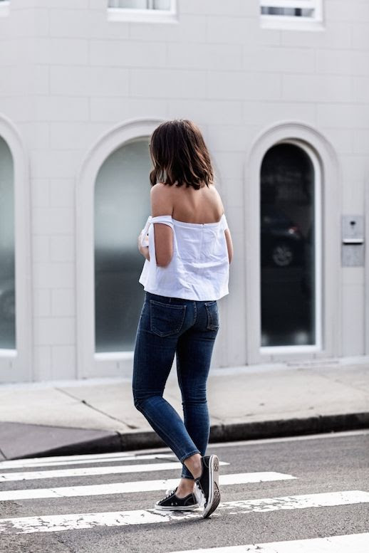 Le Fashion Blog White Off The Shoulder Top Tie Up Sleeve Dark Jeans Black Sneakers Via Harper And Harley