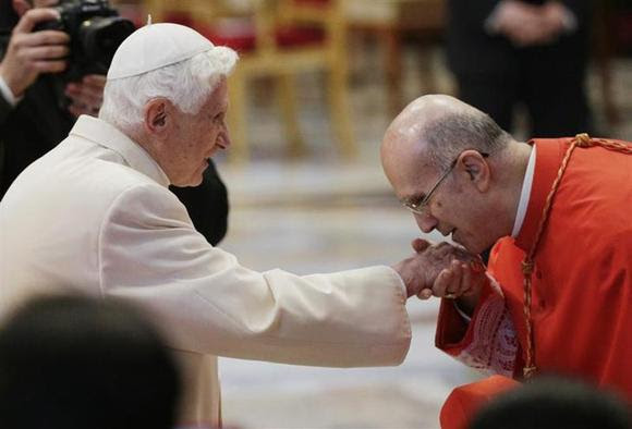 Pope Emeritus Benedict XVI is greeted by Cardinal Tarcisio Bertone (R) as he arrives to attend a consistory ceremony in Saint Peter's Basilica at the Vatican February 22, 2014. REUTERS/Max Rossi
