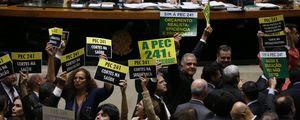 Deputados seguram placas durante votação da proposta que limita gastos públicos