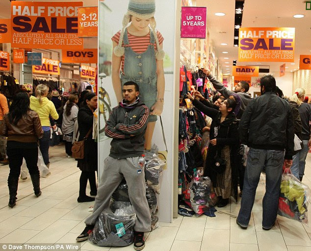 Test of endurance: One shopper looks thoroughly fed-up as he guards his shopping outside the Next Kids Boxing Day Sale at the Trafford Centre in Manchester