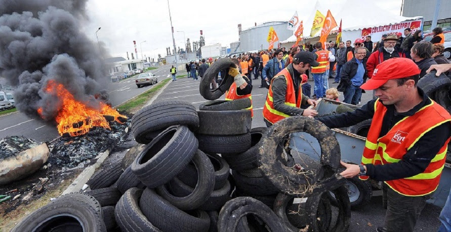 epa02399672 Workers on strike burn tires as they block the access of Total oil refinery in Donges, France, 18 October 2010. Many oil refineries and fuel depots have been blocked in France by demonstrators who oppose the government pension law, causing fuel shortages.  EPA/MAXPPP/FRANCK DUBRAY FRANCE OUT, BELGIUM OUT