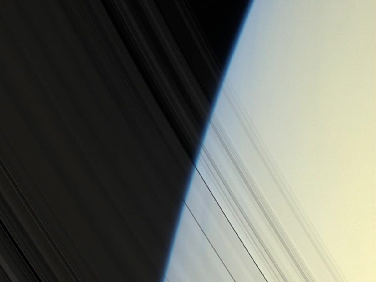 The planet's inner C-ring is almost translucent in this photo, showing the blue-hazed limb of Saturn's atmosphere behind it.