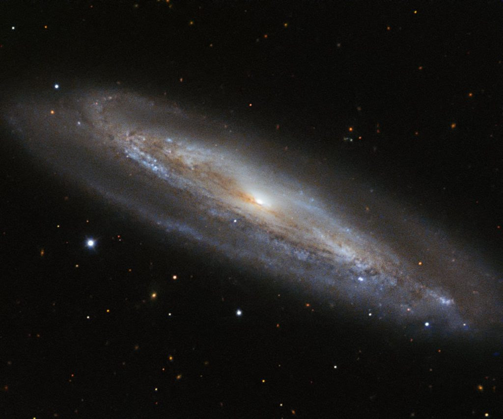 The colour blue has many associations — coldness, sadness, serenity. However, the colour holds a completely different meaning for astronomers, as demonstrated by the edge-on spiral galaxy  Messier 98. Messier 98, also known as NGC 4192, is located approximately 50 million light-years away in the constellation of Coma Berenices (Berenice's Hair). In this spectacular image from ESO's New Technology Telescope (NTT), the galaxy's perimeter, rippled with gas and dust, is dotted with pockets of blueish light. These are regions filled with very young stars, which are so hot that they glow with a bright blue hue. These young stars are burning at such high temperatures that they are emitting fierce radiation, burning away some of the dense material that surrounds them. In total, Messier 98 is thought to contain one trillion stars! The NTT is a 3.58-metre telescope at the La Silla Observatory, which pioneered the use of active optics and was the first in the world to have a computer-controlled main mirror.