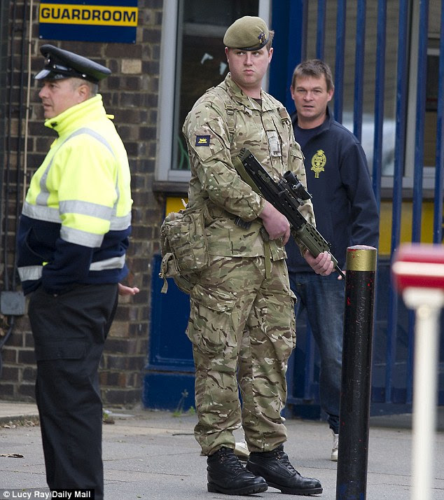Patrol: An armed soldier stands guard outside the Royal Artillery Barracks in Woolwich, south-east London