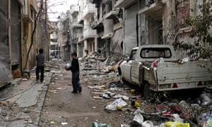 Children play on a street of damaged buildings in the besieged city of Homs