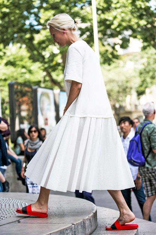 Le Fashion Blog Easy All White Look Street Style Low Blonde Bun Tee Pleated Midi Skirt Sporty Red Slide Sandals Via Sandra Semburg