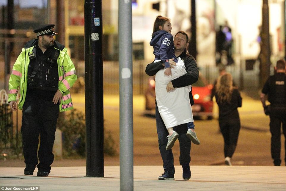 A father carries away his daughter following the suspected terror attack at the Ariana Grande concert