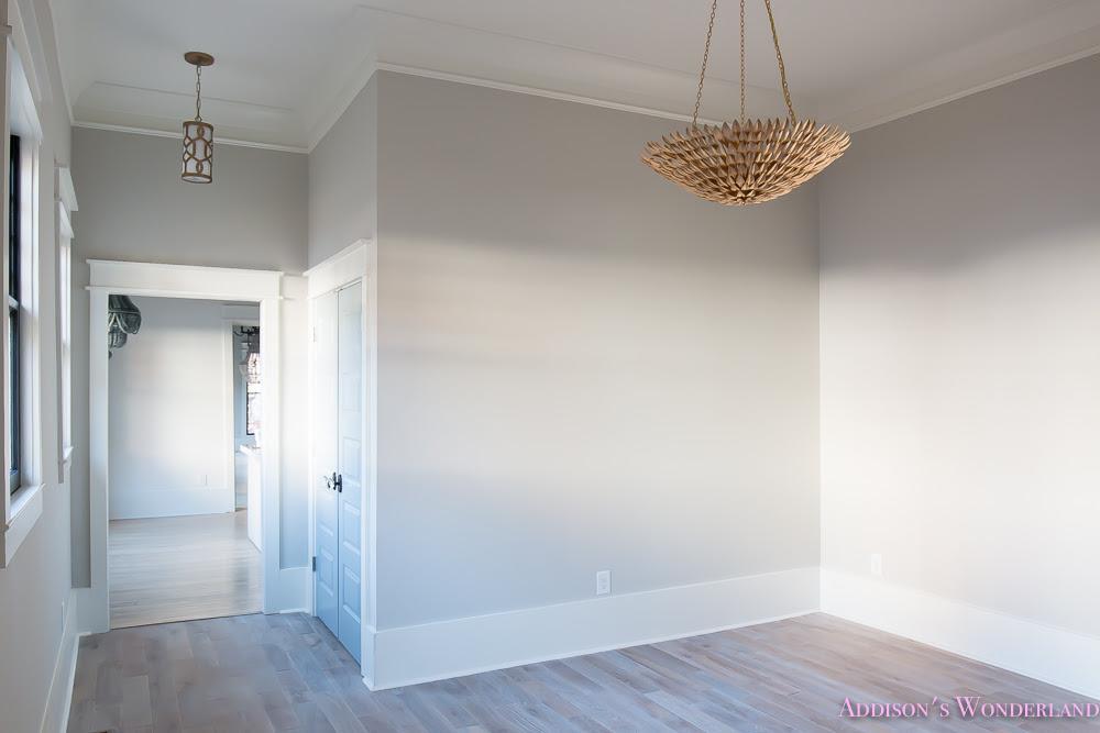 living room light gray walls grey gold chandelier black window sashes whitewashed hardwood flooring light blue doors 4 of 6