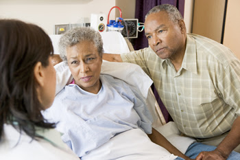 A photograph shows a woman in a hospital bed and a man standing at the bedside, holding her hand. They are listening to a health professional, who is standing with her back to the camera.